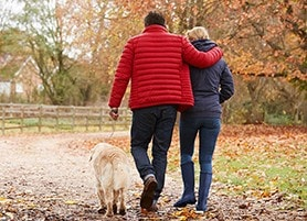 A couple walking their dog in the park