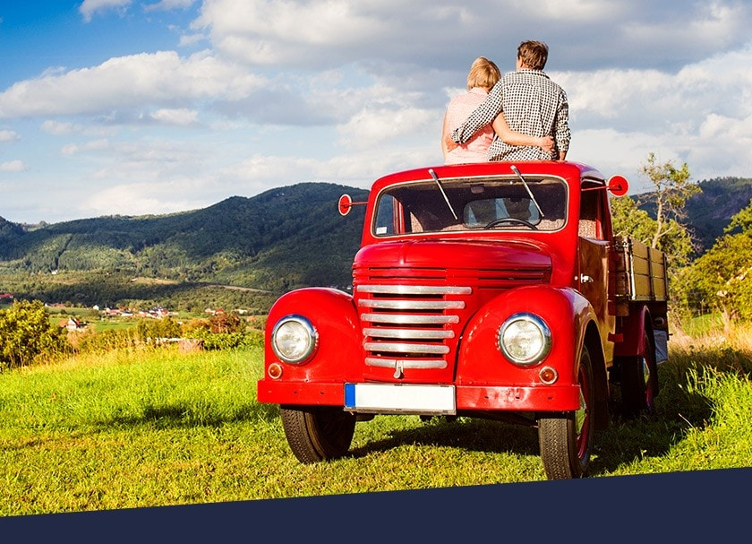 A couple sitting on the roof of a red truck in a farm field admire the landscape