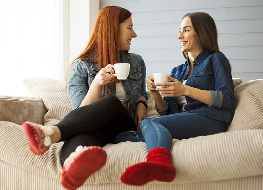 Two women chatting with coffee mugs