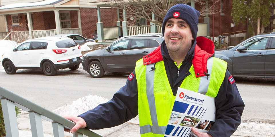 Canada Post worker delivering an envelope
