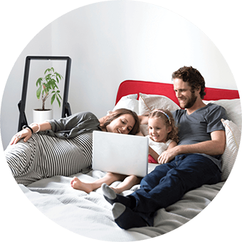 A family watches a movie together on a laptop in a bed